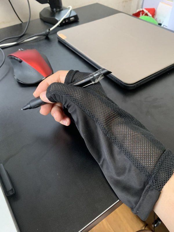 手袋をしてペンを持っている手