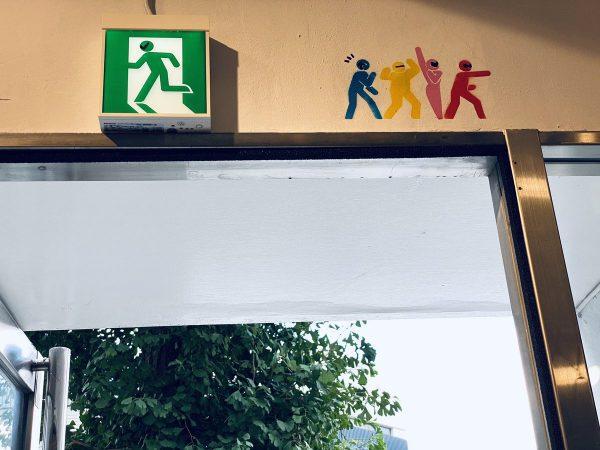 壁の非常灯と、そばに描かれた4人のレンジャーたち
