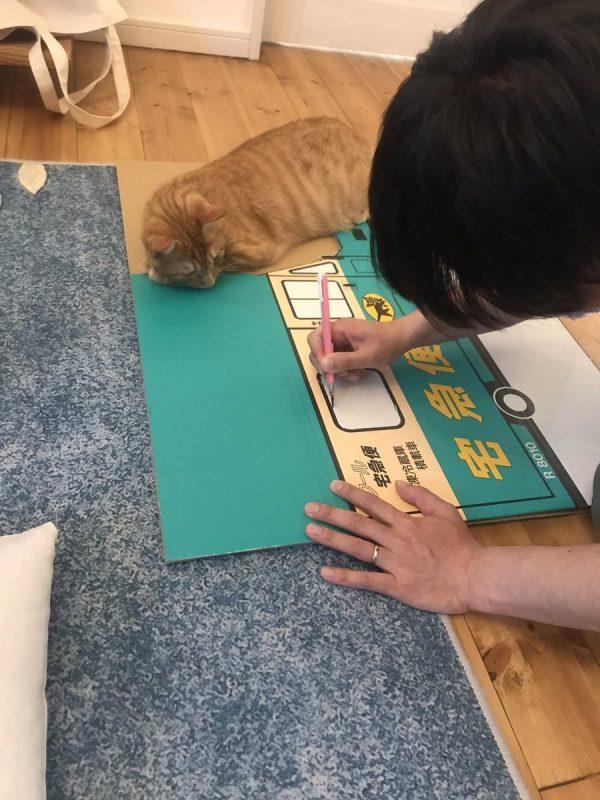 クロネコヤマトの段ボールをくり抜く夫と猫