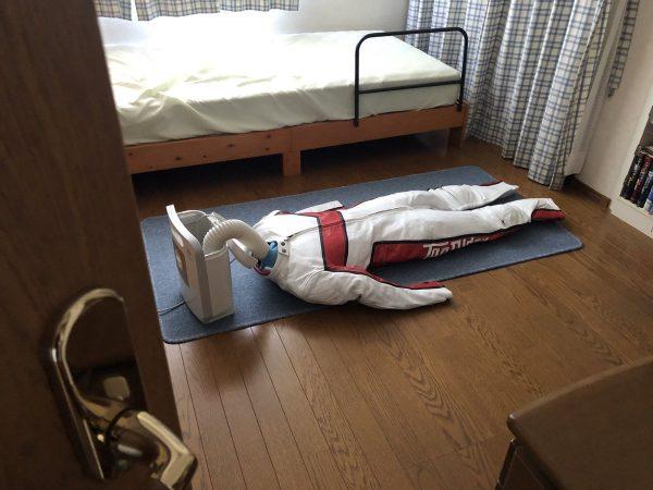 床に寝ているように見えるライディングスーツ