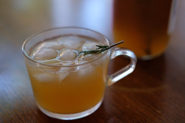 カップに入ったりんごジュースとローズマリーの枝