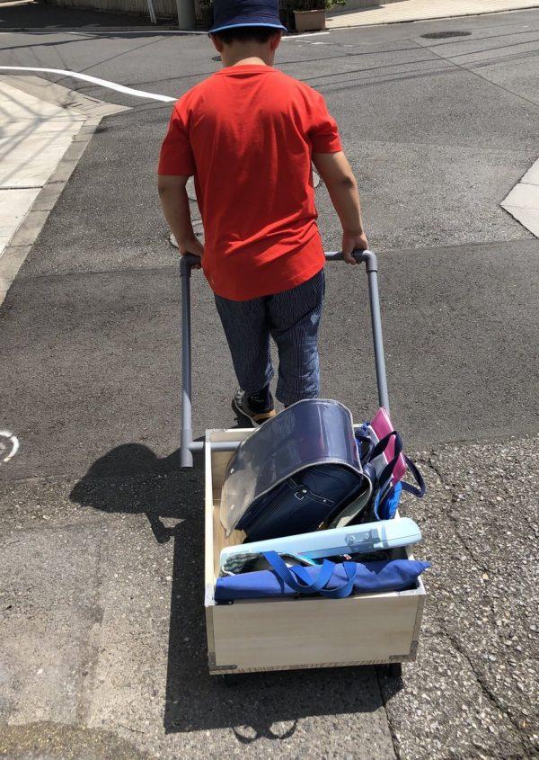 荷物を入れたリヤカーを引っ張る男の子