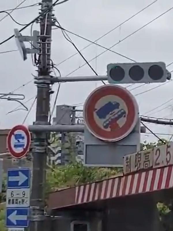 回転しはじめた「大型貨物自動車・大型乗用自動車通行止め」の標識